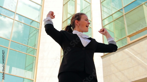 Young businesswoman showing her success near office building