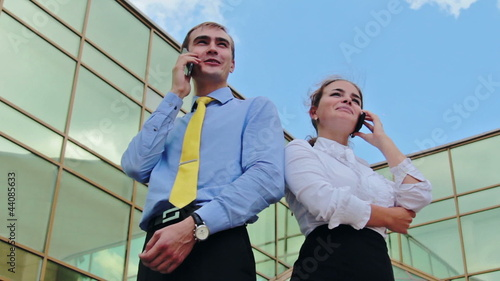 Businesspeople standing back to back and calling by cellphones