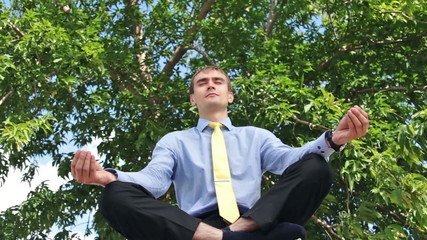 Young businessman doing yoga in the park