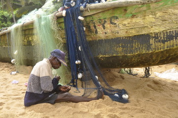 Alter Mann flickt ein Fischernetz