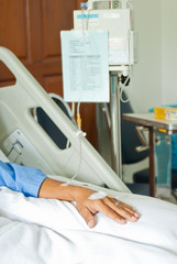Patient hand with saline intravenous (iv) on hospital bed