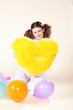girl keeps a yellow pillow in a pajamas in the form of heart