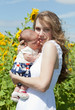 Young mother with the baby among blossoming sunflowers