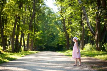 Little girl in a pink dress walking down