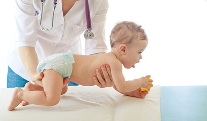 Pediatrician examining baby .