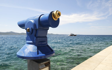 Fernrohr am Meer mit Boot und Promenade