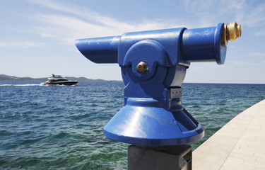 Fernrohr am blauen Meer mit Boot