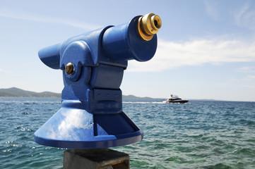Fernrohr am Meer mit Yacht