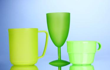 Bright plastic tableware on blue background