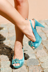 Beautiful woman legs in blue high heel shoes