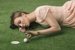 girl's lying on grass with golf ball, she hits that