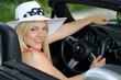 Junge blonde Frau mit Sommerhut im Cabriolet