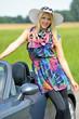 Junge blonde Frau lehnt sich an ein Cabriolet