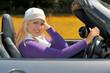 Blonde Frau fährt im Herbst ein Cabrio