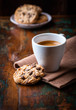 Cup of espresso and chocolate chip cookies on wooden table