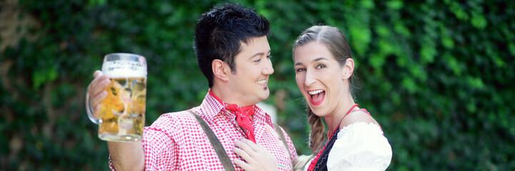 Paar prostet in Lederhosen und Dirndl