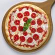 Pizza ai pomodorini intera su pala di legno