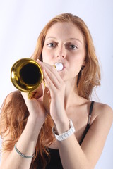 Pretty redhead woman playing the trumpet