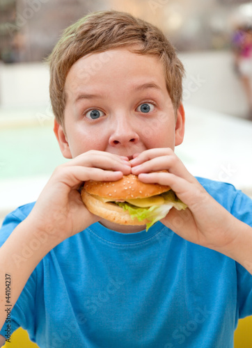 boy in cafe eating hamburger