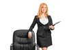 A businesswoman with clipboard standing next to a chair