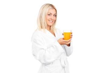 Young woman in bathrobe drinking orange juice for breakfast