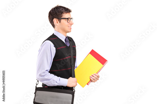 A student walking with notebooks in  his hand