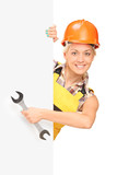 Female construction worker holding a wrench behind panel