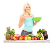 Woman eating a salad, standing behind table full of fruits and v