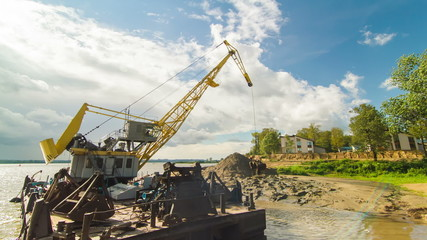 Floating crane digging sand on river side