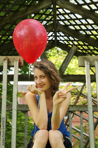 Teen with a balloon doing victory sign