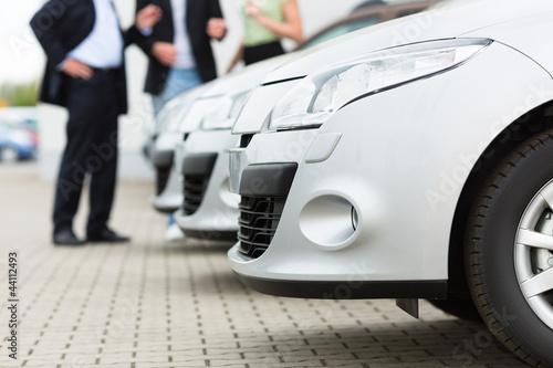 Autohändler und Kunden schauen ein Auto an