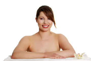 Beautiful naked woman sitting in spa room and smiling.
