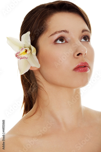 Beautiful naked woman with orchid flower in hair.