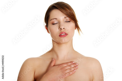 Naked woman standing with hand on her chest.