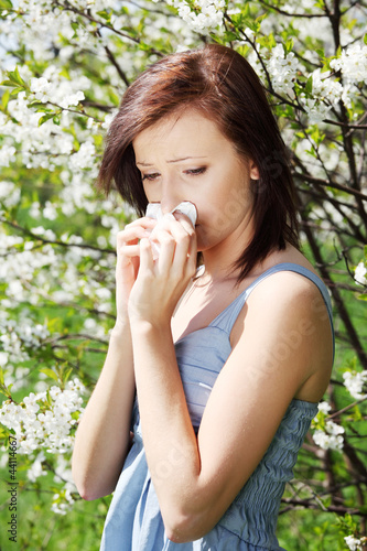 Girl with runny nose, having allergy among flowers.