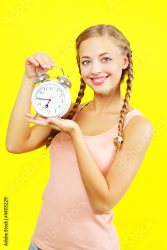 Beautiful young girl holding an alarm clock on yellow