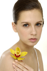 skin of her face with a yellow orchid