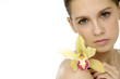 woman with a wellness skin of her face with a yellow orchid