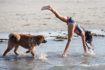 Mädchen macht neben ihrem Hund einen Handstand