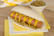 Simple Hot Dog with yellow mustard and caramelized onions.