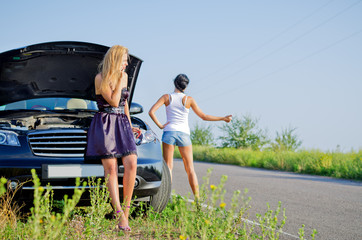 Women hitchhiking after a breakdown