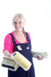 Happy woman decorator holding a roll of wallpaper