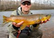 Fly fisherman holding a huge Brown Trout fish - 44124672
