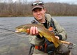 Fly fisherman with Brown Trout, fly rod and reel, in a river - 44124678