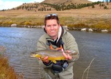 Man holding a brown trout caught fly fishing on a stream