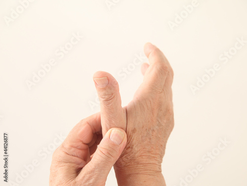 a man holds his aching thumb