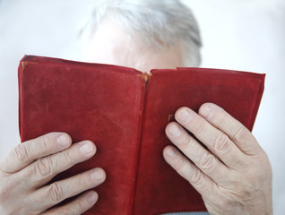 senior reads an old red leather-bound book