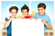 Three boys in classroom holding white clean board