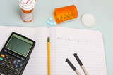 Calculator, pills, compass & pencil on composition book