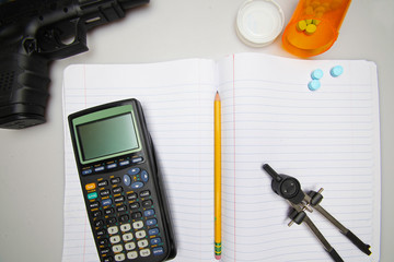 Automatic Firearm, Calculator, Compass, Pill on Composition Book